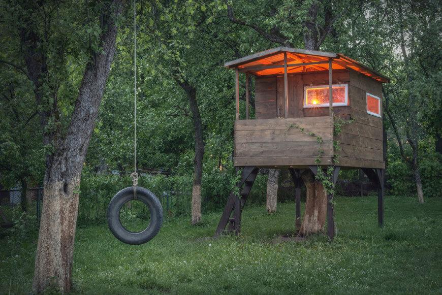 Une balançoire à pneus est le complément parfait à cette simple maisonnette en planches.  D'une simplicité trompeuse, cette structure a en fait été construite autour d'un arbre.