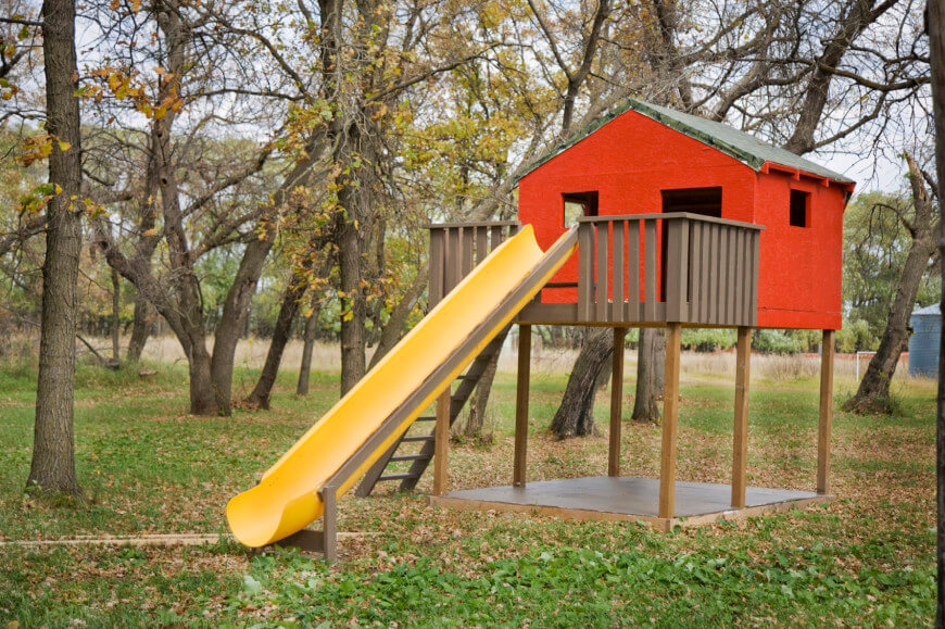 A bright yellow slide makes for a great exit from this stilted structure. Also the concrete pad beneath the structure also serves as a great mud-free play area.