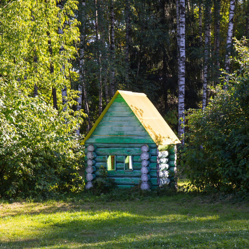 Add color to a log cabin playhouse for a touch of whimsey. The yellow roof complements the pale green chosen for this rustic playhouse.