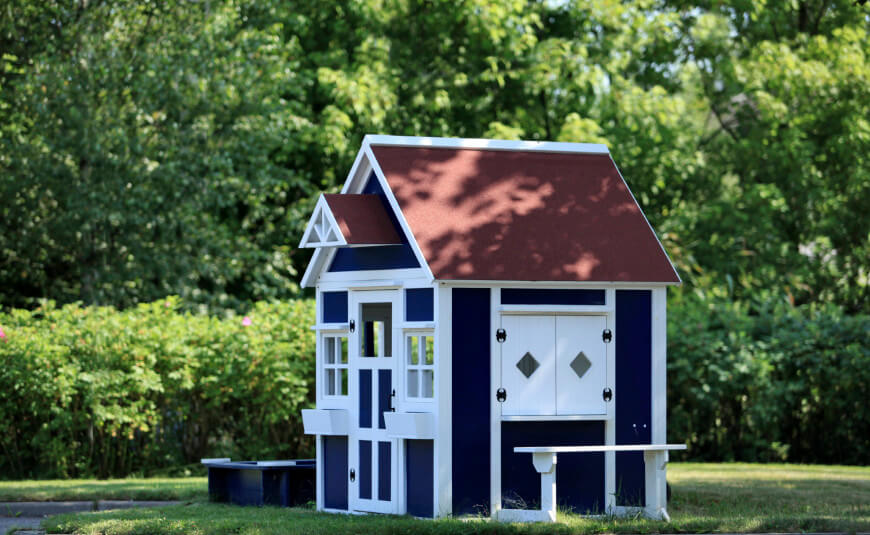 Wooden shutters and window boxes make this miniature playhouse look just like home. Including window boxes and a bench are excellent additions for kids to enjoy.