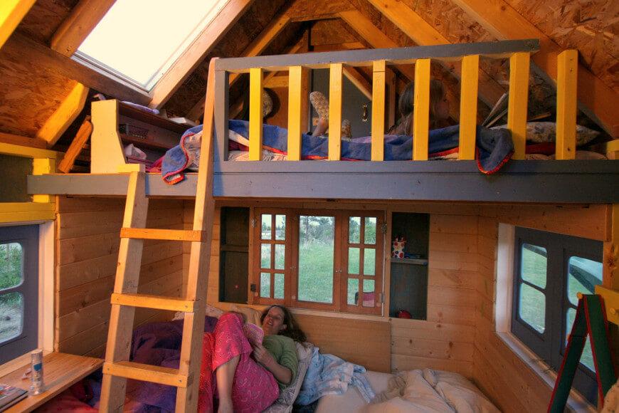 Une vue de l'intérieur de cette maisonnette montre que l'ajout d'un loft laisse beaucoup d'espace pour jouer et dormir.  Quel super endroit pour accueillir une soirée pyjama.  On peut presque entendre les histoires de fantômes!