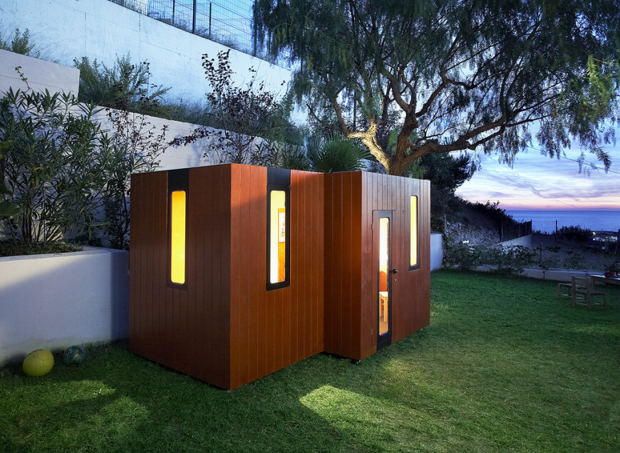 A warm glow emanates from another modern looking playhouse. This type of playhouse is the perfect complement a modern concept yard or home.