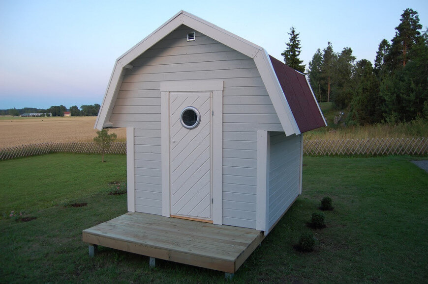 The modern style door, and front porch give an interesting contrast to this otherwise simple barn shaped playhouse.