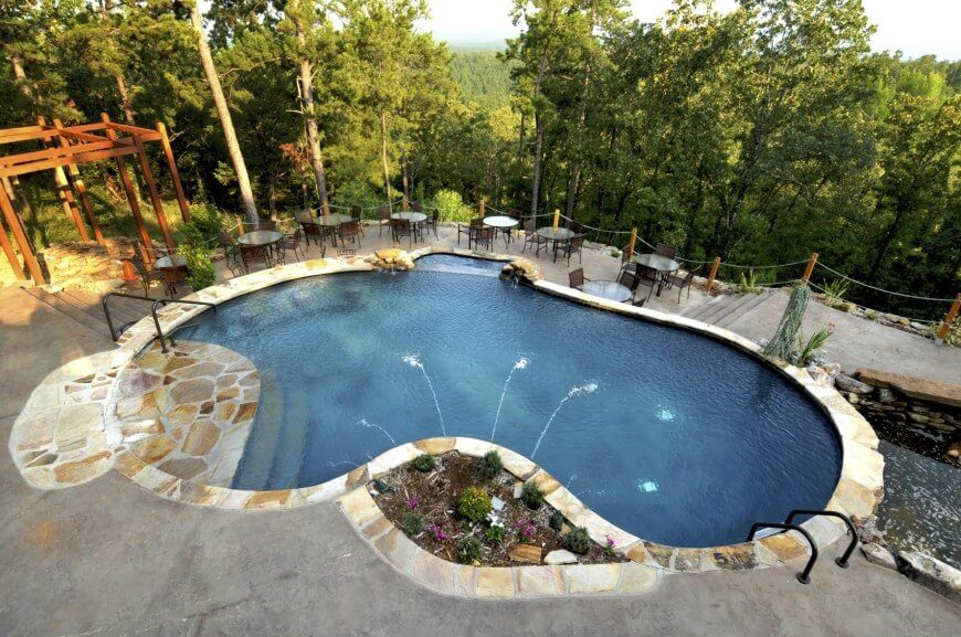 Here Is A Concrete Pool In The Traditional Kidney Shape, With A Water  Feature.