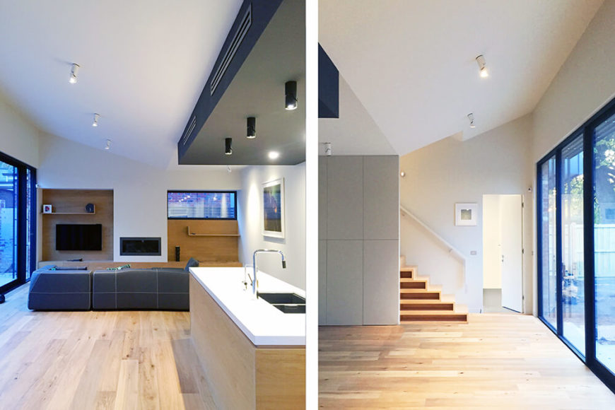 In this split screen shot, we take a look at the large central open space from two angles. First, we see the living room set back beyond the large kitchen island. Second, we see the stairs toward the bedroom area of the home, as well as one of the large sets of sliding glass doors.