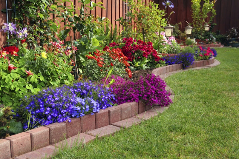 Here Is A Brick Lined Flowerbed Against A Fence In This Yard. Placing A  Flower