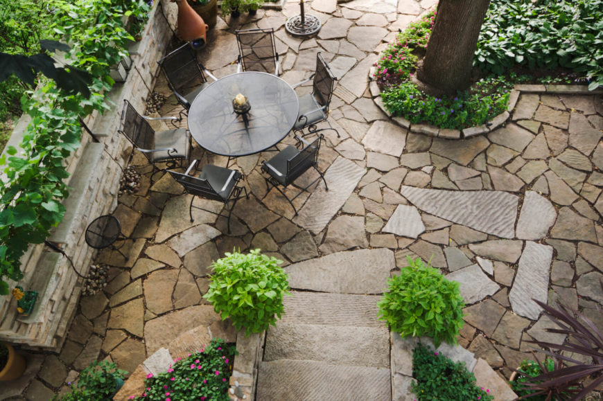 Stone can blend nearly without seam when it is combined with a patio design that matches. Flower bed, floor, and steps all become one cohesive and unified design.