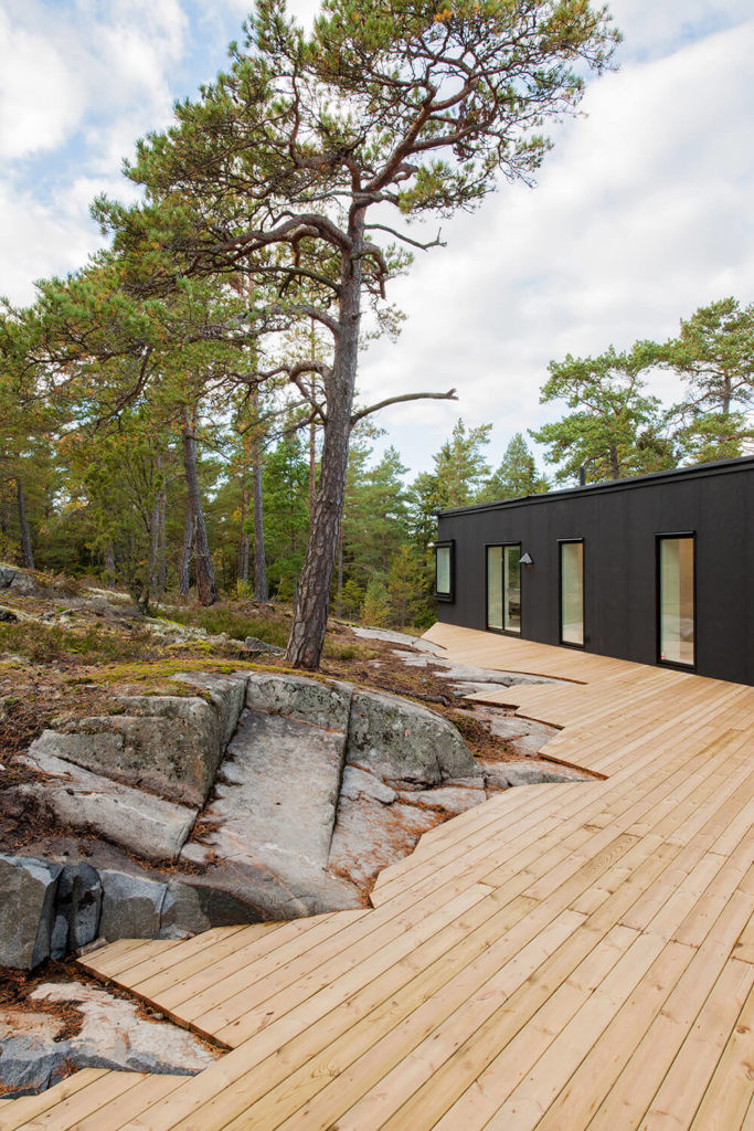 The clean lines of the deck contrast perfectly with the angular, organically cut outer edge, which mirrors the shape of the surrounding rocks. The deck also offers a warm counterpoint to the black of the house facade.