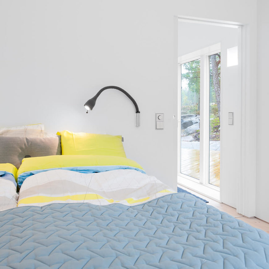 The master bedroom features subtle use of color, with light blue and yellow bed sheets paired with the same white walls seen elsewhere in the home. Through the doors at right, we can see large glass sliding doors that lead to the patio.