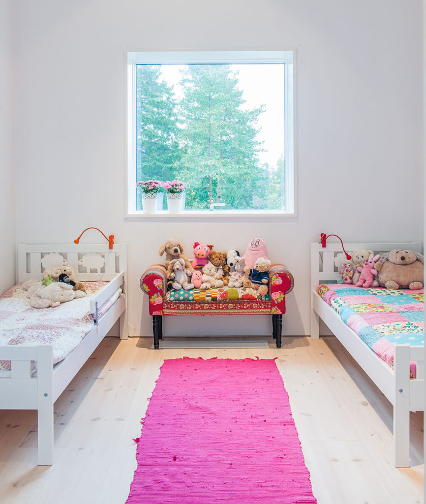 This children's bedroom features more subtle splashes of bright color, including a bold pink rug at center. As seen here, the large windows throughout the home offer a bounty of natural lighting across the brightly designed interior.