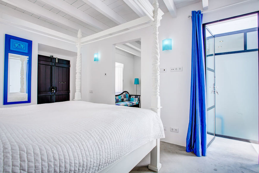 The adjacent bedroom shares this bold yet restrained blue palette, sporting a shade darker on the mirror frame and bathroom access curtain. The white tones make these subtle appearances of color truly pop.