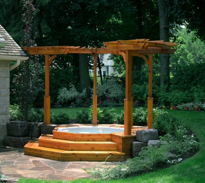 This version is built into a raised stone garden bed and is covered by a curved pergola structure.