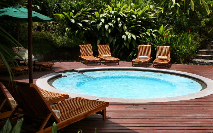 An in-ground hot tub, like a swimming pool, is a great place to arrange patio furniture around. Climbing in and out of this hot tub is easy, and you don't have to be away from your friends and family when you want to take a soak.