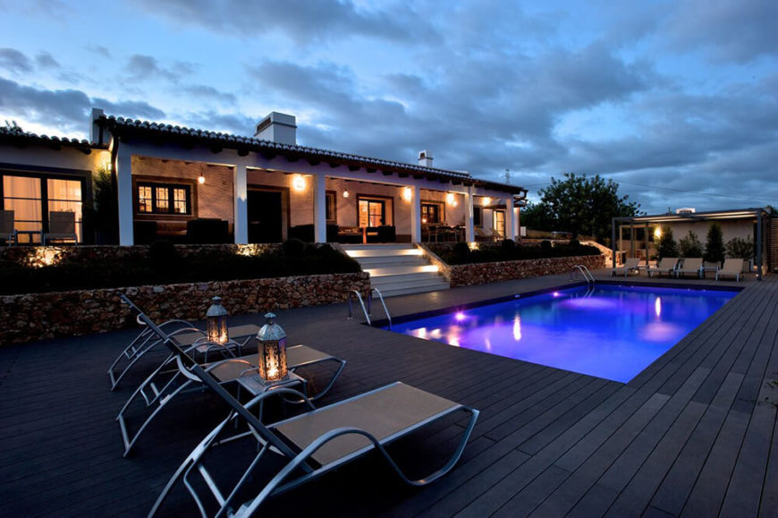 Out back, we see the massive deck sprawling to both ends of the property, with a decent sized pool at center. The dark wood planks match the rich colors of the landscape well.