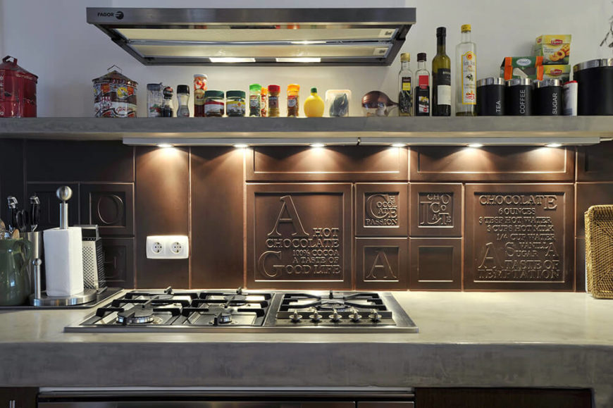 Above the built-in range we see this unique backsplash, a lavish ode to the pleasures of dark chocolate. Above, a lengthy open shelf houses all of the necessary spices for this well-equipped kitchen.