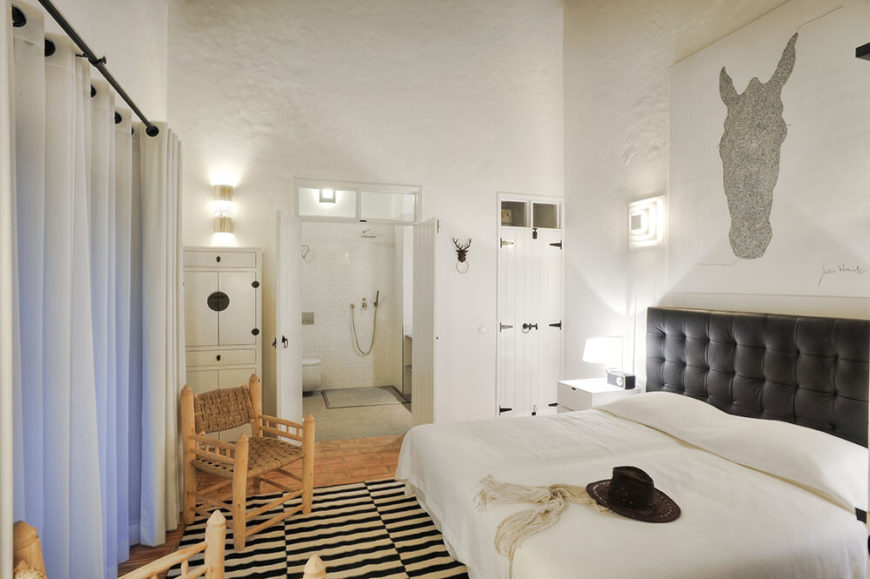 Finally, here's the master bedroom en suite, with a pair of white double doors leading to a private bathroom. Abundant storage, lighting, and a variety of texture makes for a luxurious space.