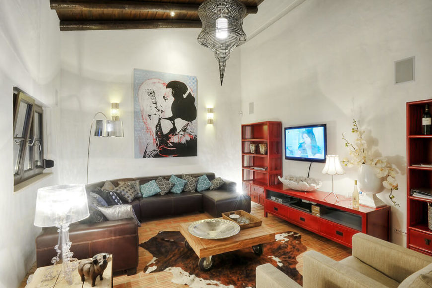 The living room is packed with detailed and colorful furniture, from a dark leather sectional sofa to bright red media shelving and entertainment stand. At center is a rustic industrial wood coffee table, anchoring the disparate space.