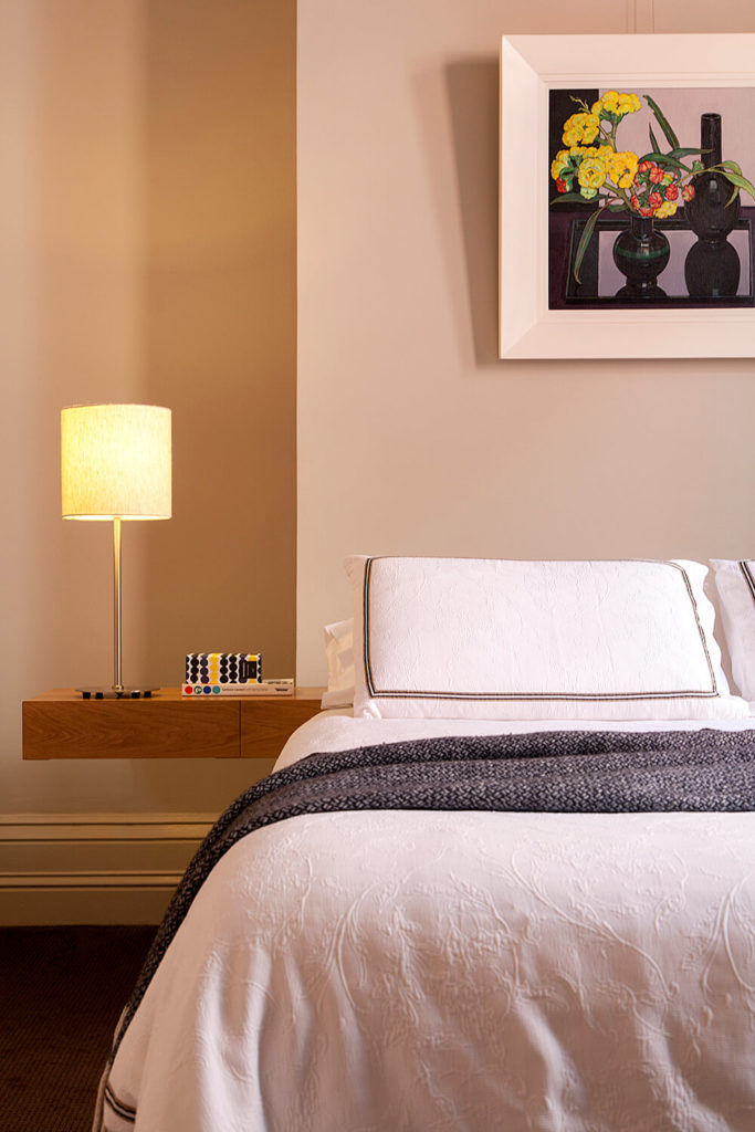 The bedrooms share the sleek minimalism of the living room area, with innovative wall-mounted bedside tables. The light natural wood acts as a fine counterpoint to the modern construction.