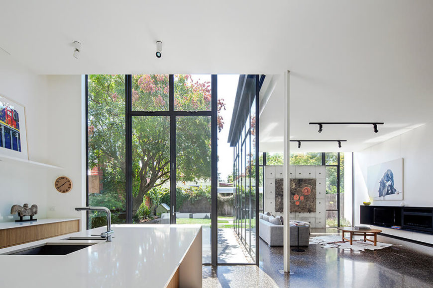 The large, open plan space contains the living room, dining, and kitchen functions within the same set of walls, all sunlit through the full height glass exterior walls. Spare placement of furniture and minimalist decoration leaves room for the artwork to stand out.
