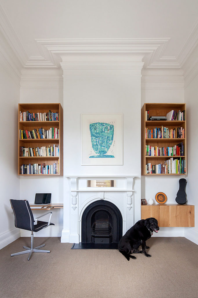In this updated room, we see the original fireplace surround reading toward the high ceiling, yet it's bracketed by sleek natural wood shelving and cabinetry. The eclectic mixture of traditional and modern makes for a fascinating space.