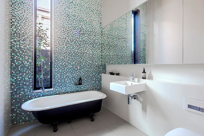 The master bath also features an intricate tile wall, this time providing a wash of color in the white space. Frameless mirrors and a claw foot bathtub make for intriguing juxtapositions in this modern space.