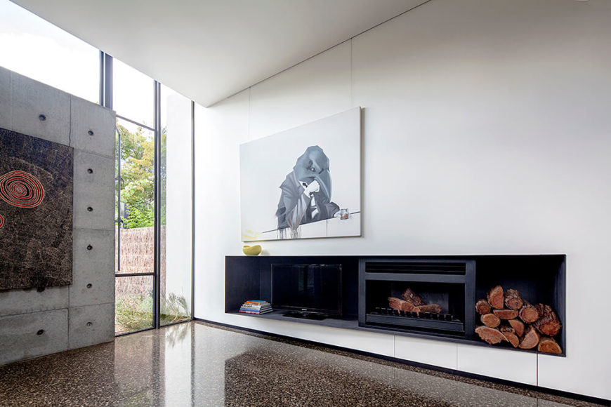 Along the white wall, we see the embedded entertainment shelf that also contains a fireplace and space for firewood. This singular interruption on the white walls is complemented by another large painting above.