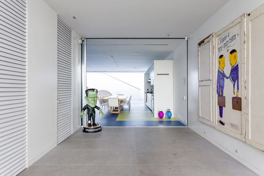 Moving down the hall from the large open room, we see more artwork and subtle bursts of color among the white walls and concrete flooring.