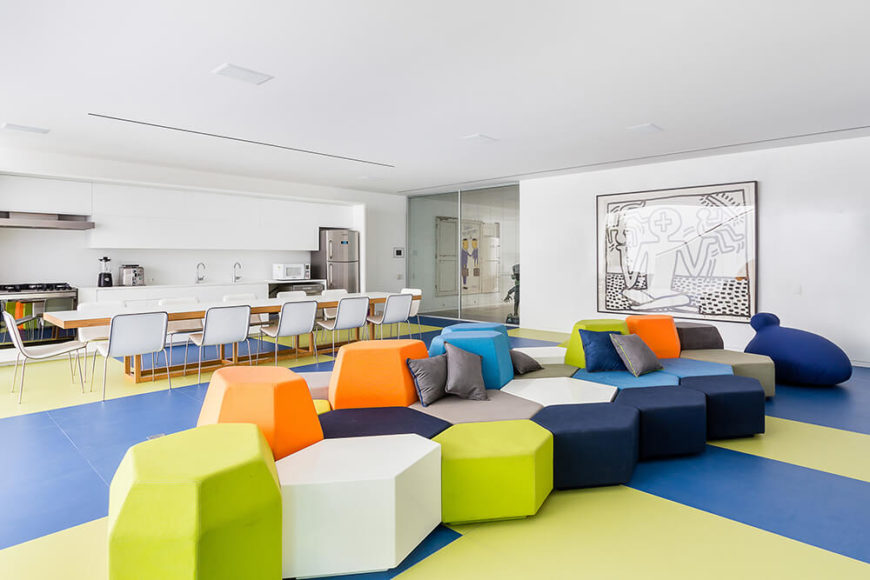 The massive, open plan center of the lower level is this vast play area, replete with geometric blocks in an array of colors over a two-tone set of flooring. The kitchen and lengthy dining table add a dose of function. To the right, we see a large Keith Haring painting.