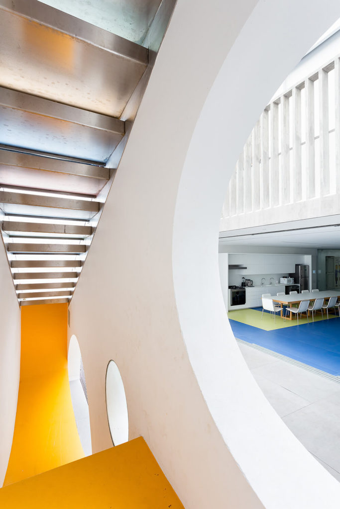 Just outside the Toy House, connecting with the main building, is the large steel staircase. Below we see the bright yellow slide, adding an element of playfulness and whimsy to the trip between the structures.