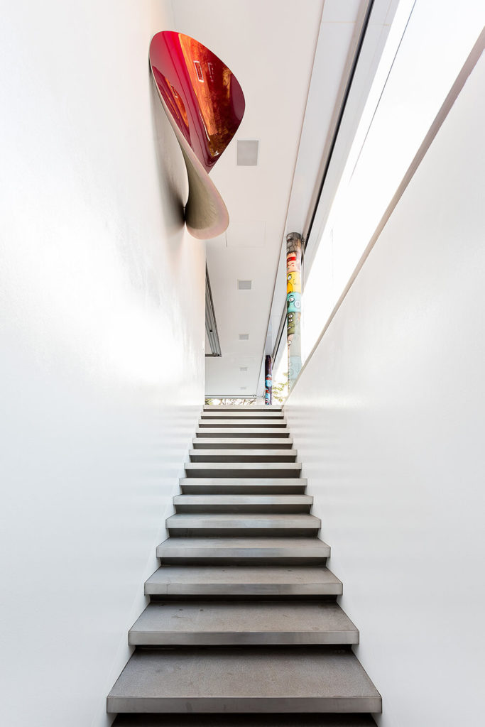 Here are the concrete stairs leading to the upper level of the Toy House. Between these white walls, we can see the bursts of color, courtesy of various art pieces, on the pillars above.