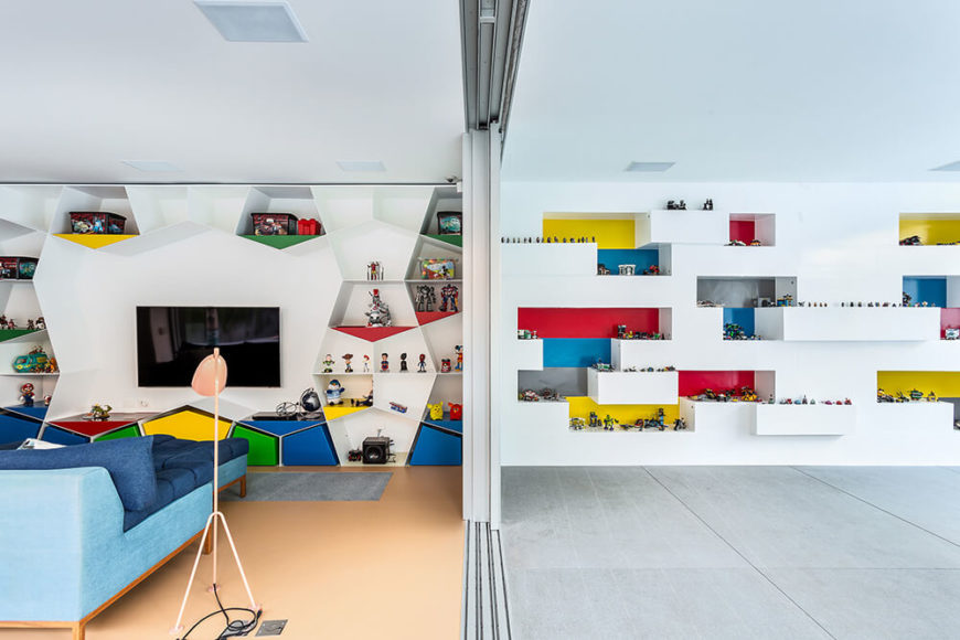 """The living room on this floor features an idiosyncratic, polygonal shelving wall dotted with bright primary colors. To the right is the distinctive """"Lego"""" wall, with built-in shelving for hundreds of toys."""