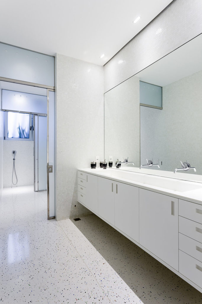 The bathroom in the Toy House doubles down on the sleek, modern, and white look with a textural floor and micro tile wall near the shower functions.