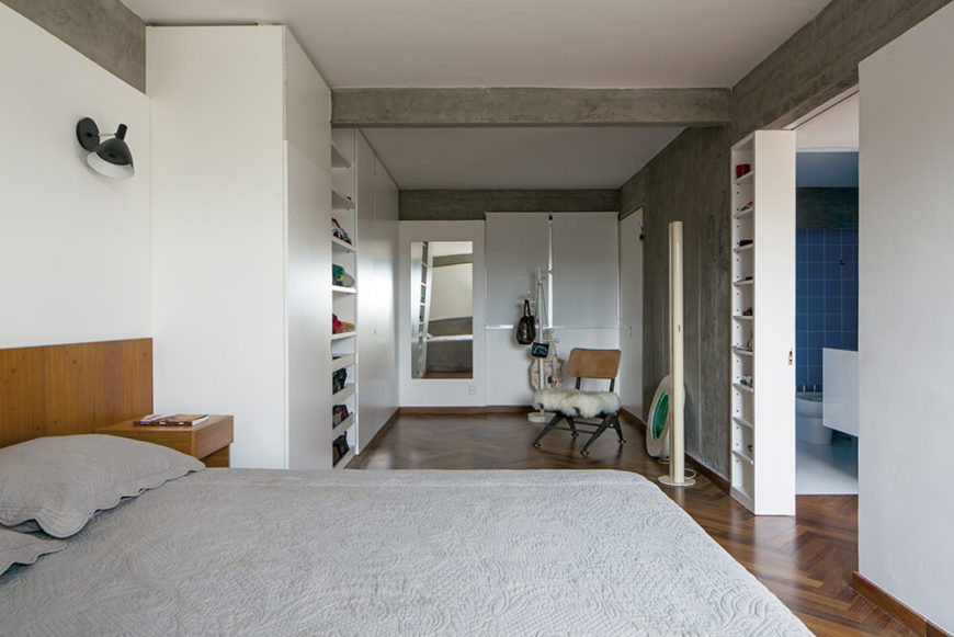 The master bedroom features a lengthy relaxing space beyond the bed, with built-in shelving for clothes and other items. A singular wooden chair with a white fur seat stands in the open space.