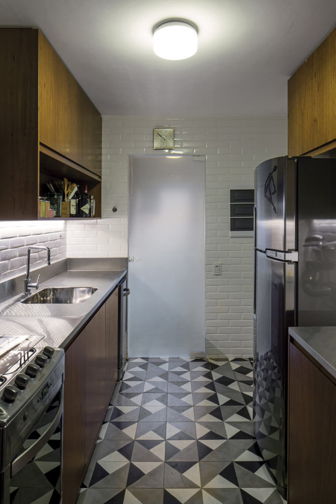 The kitchen defines itself as distinct from the rest of the home with bold geometric tile flooring, white subway tile walls, and sleek stainless steel countertops.