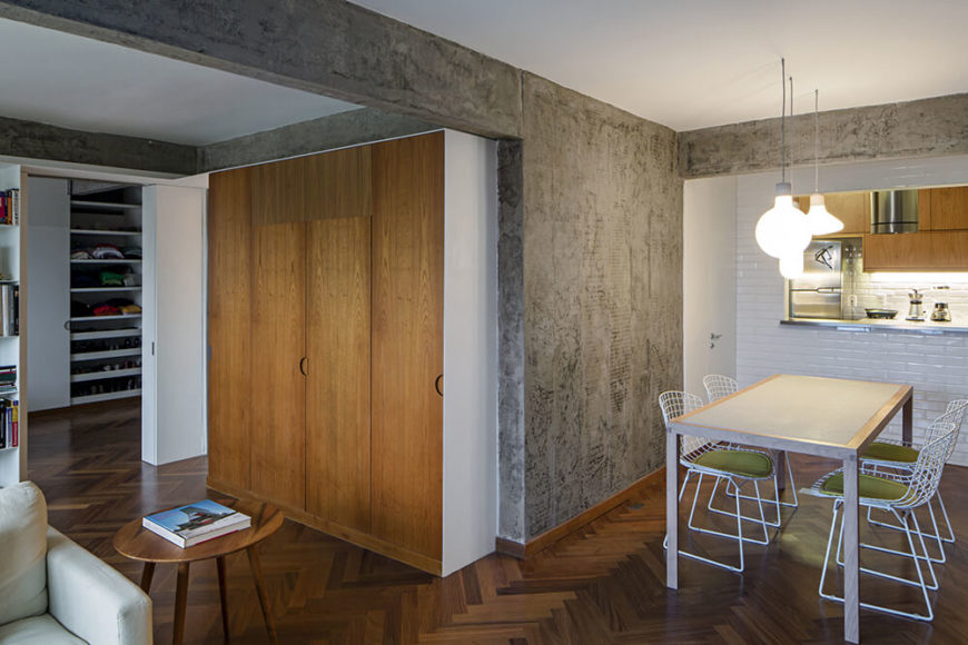 The living room is part of a larger open space at the center of the apartment, connecting a dining area and kitchen as well. Here we see the original concrete standing out proudly between swaths of white walls.