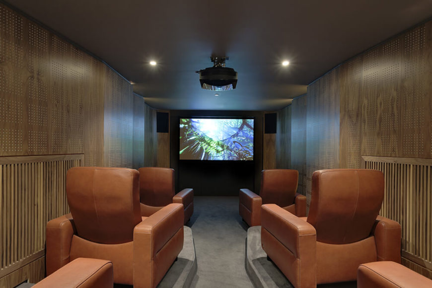 In the lower level, we see far more of the rich wood paneling. This is the cinema room, fitted with purpose built chairs for movie watching, as well as a projector and massive screen at the far end.