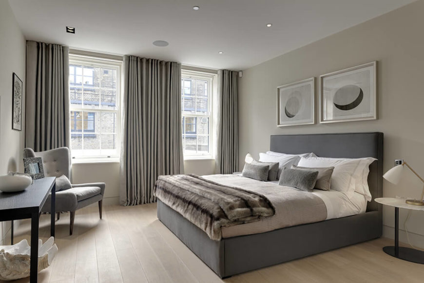 The master bedroom features a muted color palette, similar to the elegant tones seen throughout the rest of the home. With a pair of more standard shaped windows, this area is the most traditionally built in the home.