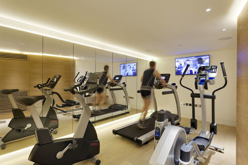 Next to the cinema room, we see the fully equipped home gym, featuring both natural wood paneling and full height, frameless mirrors bracketing the space.
