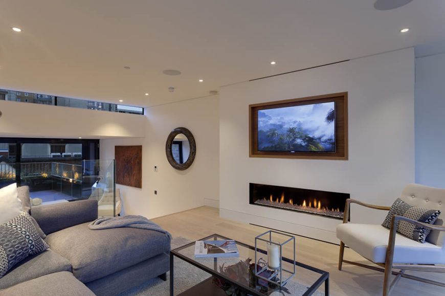 Moving up a floor, we see the distinctly layered construction of the house sprawling linearly between the narrow walls. In this living room area, contemporary furniture meets light hardwood flooring and spare placement of art objects.