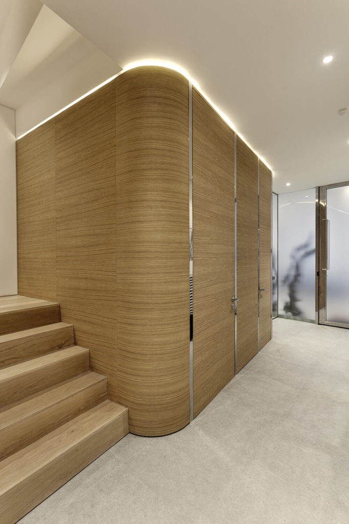 On the lower level, we see the light natural wood accents become a major force in the design, wrapping organically around the central elevator core.