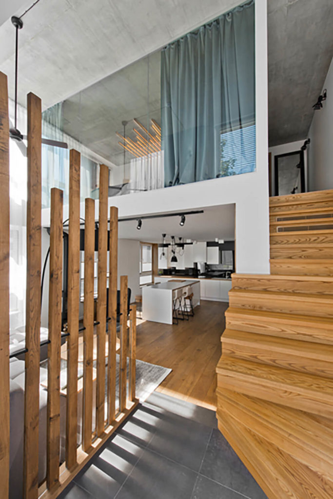 This image, taken from the open space near the staircase, captures the full height of the living room as well as the all-glass wall overlooking this area from the second floor. The mixture of neutrals and rich wood tones creates an elegant palette.