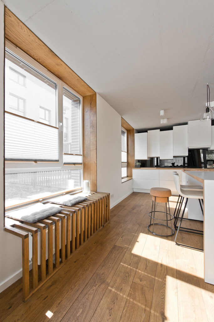 Along the exterior wall, the same natural wood as the flooring can be seen framing the large windows and providing a radiator cover and seating space here at the left.