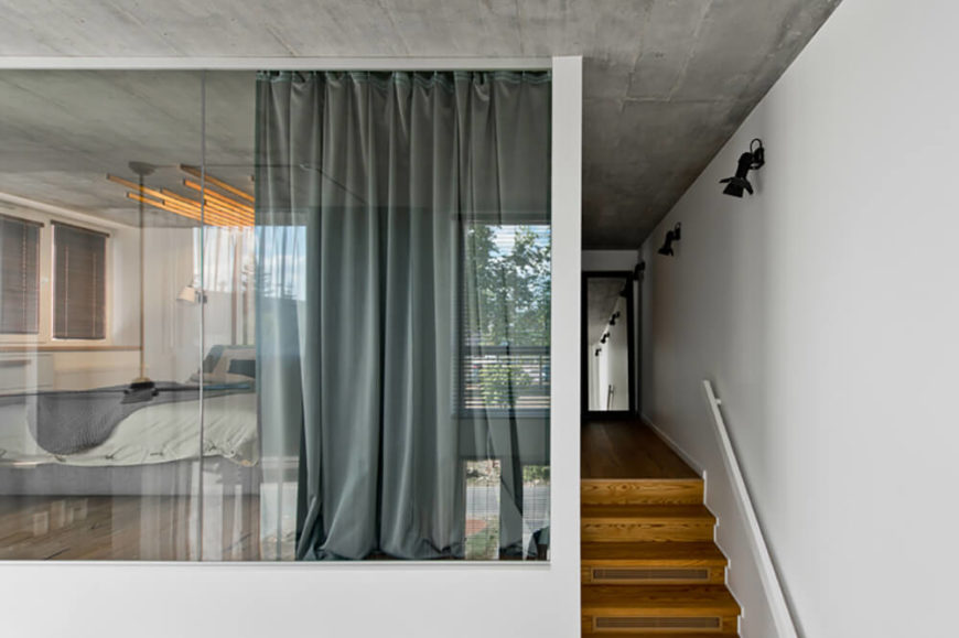 The upper level can be seen down the lengthy hallway at the top of the stairs, and right through the full heigh glass panels surrounding the master bedroom, at left.