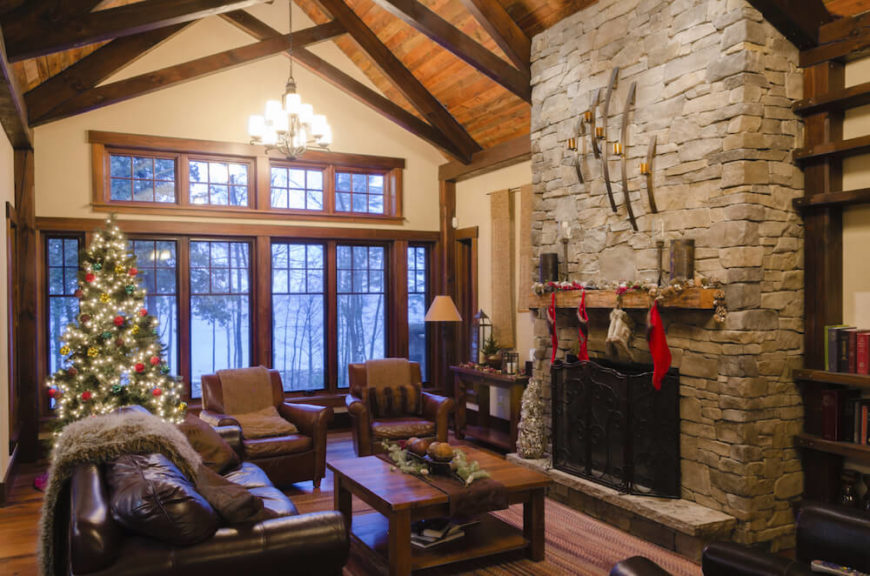 Stacked stone fireplaces have rustic appeal, and when paired with a rustic wooden mantle and wrought iron fireplace screen, it cuts an imposing figure.