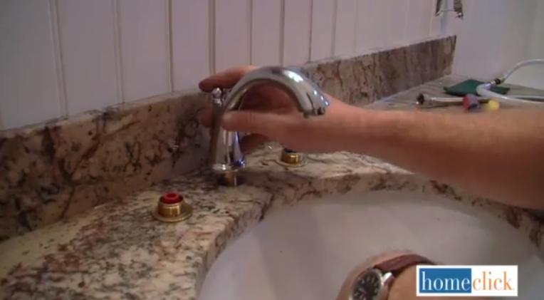 Now you're going to get started on the new sink hardware. At this point, you can insert the stem of the spout through the middle hole and secure it to the mounting bracket using the included brass nut. Make sure it's tight as can be, because this is the core of your new faucet.