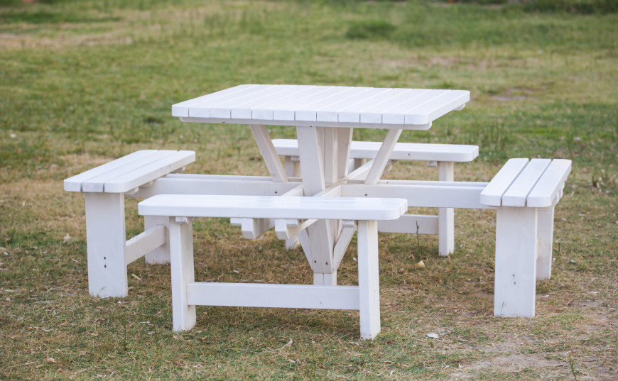 Here is another picnic table that is square. This table has attached benches. Attached benches can be useful to keep a table balanced. With the benches providing stability, the table requires less material underneath itself. This can also provide nice legroom.