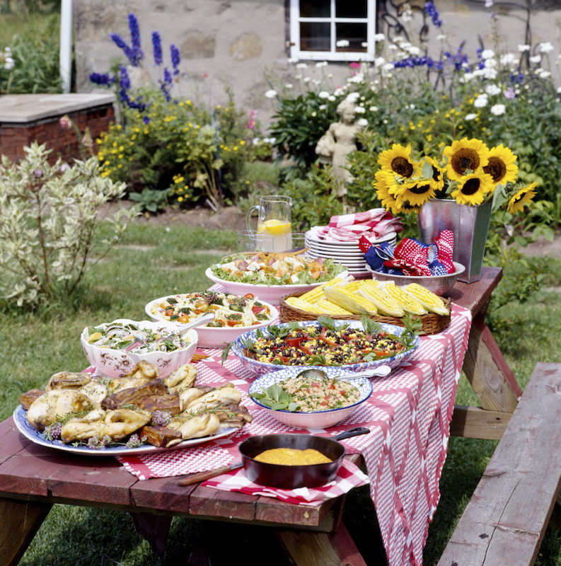 This picnic table is laden with tons of delicious food and a large bouquet of sunflowers is the perfect spot to share a meal with friends and family.