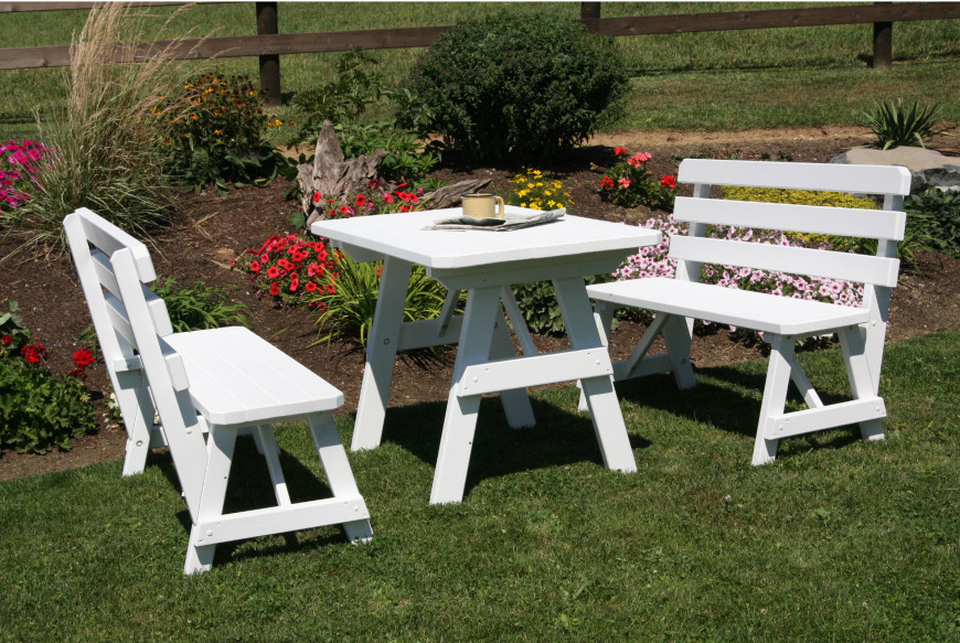 Here is a very small picnic table out by a flower garden. This is a bright and clean choice for a breezy area. White is a color that is often perfect for light and welcoming spaces.