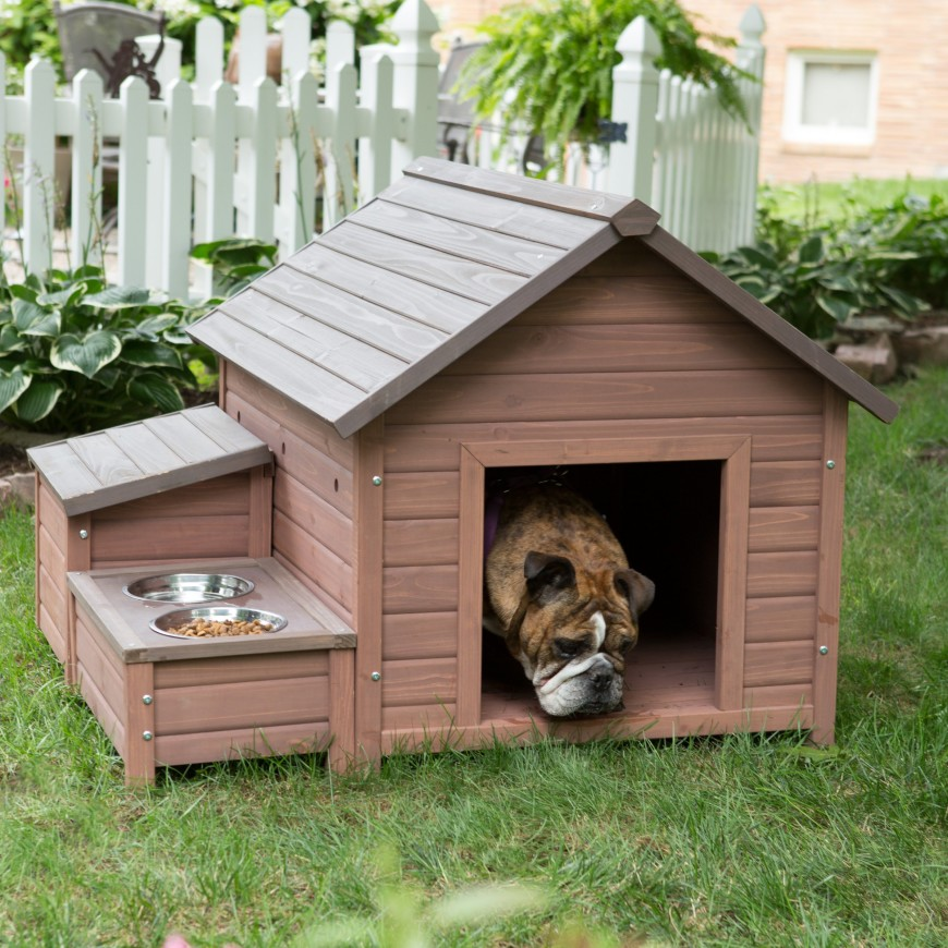 A quaint dog house with a built-in food and water dish holder on the side. The structure is classic and has plenty of space for a small dog.