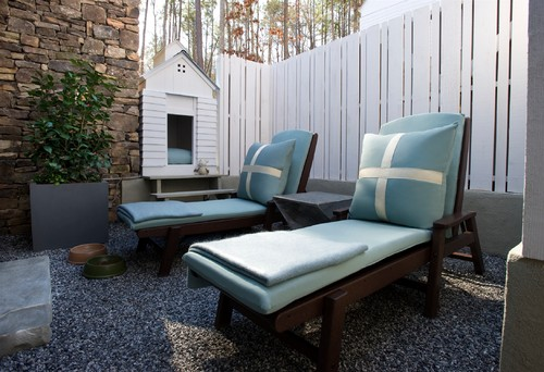 Even if you don't have a lot of space in your backyard, building a small, cozy dog house for your pooch to hang out in can be done. This one is elevated slightly to match the height of the privacy fence.
